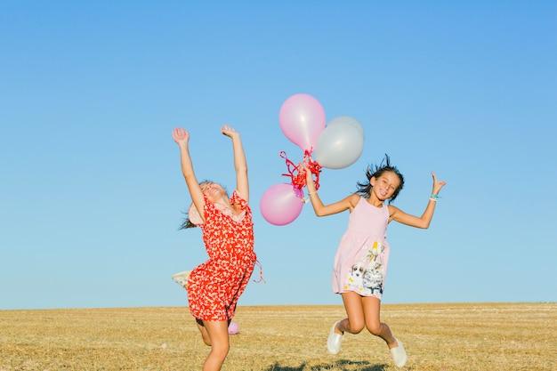 Chicas saltando con globos