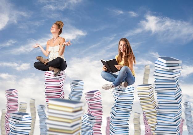 Chicas sentada sobre montañas de libros