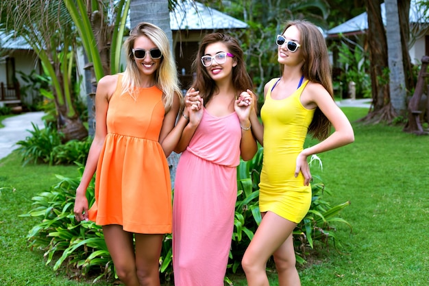 Chicas sexy mejores amigas divirtiéndose en vacaciones en un exótico país tropical caliente, vistiendo vestidos de playa vívidos hipster brillantes, emociones felices, sonriendo y riendo, fiesta en el jardín, relax, baile, alegría.