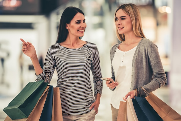 Las chicas sonríen mientras hacen compras en el centro comercial