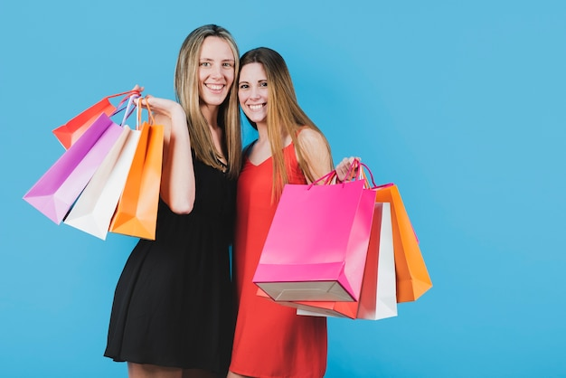 Chicas sonrientes con bolsas de compras