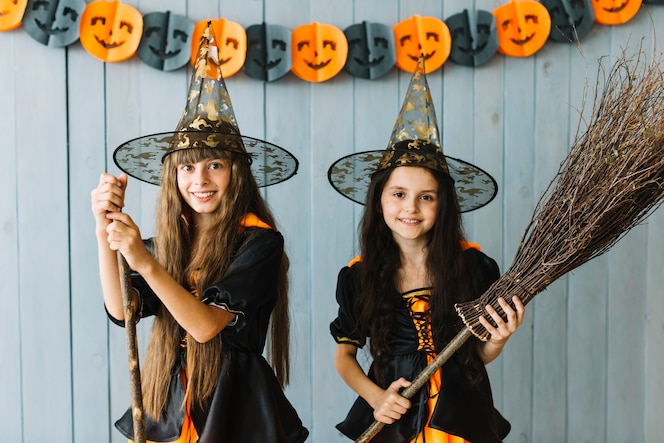 Chicas sonrientes en trajes de bruja con palo de escoba y palo