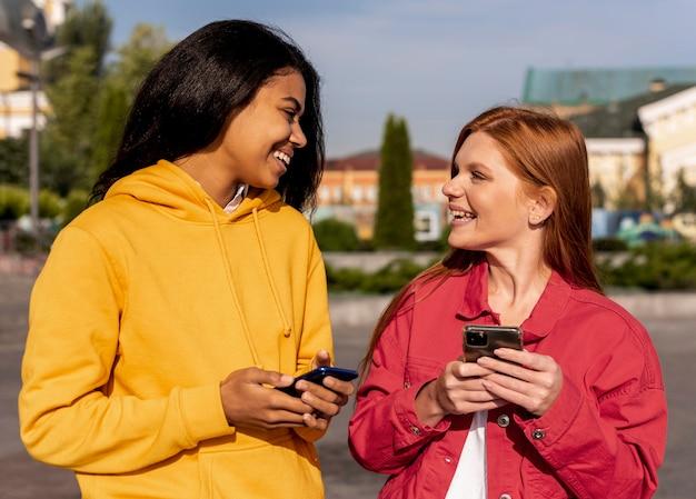 Chicas sonrientes revisando sus teléfonos
