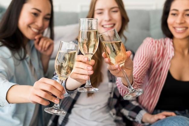Chicas sonrientes y sentadas sosteniendo copas y tintineando juntas