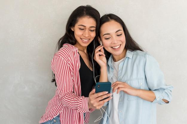 Chicas sonrientes sosteniendo un teléfono inteligente y escuchando música