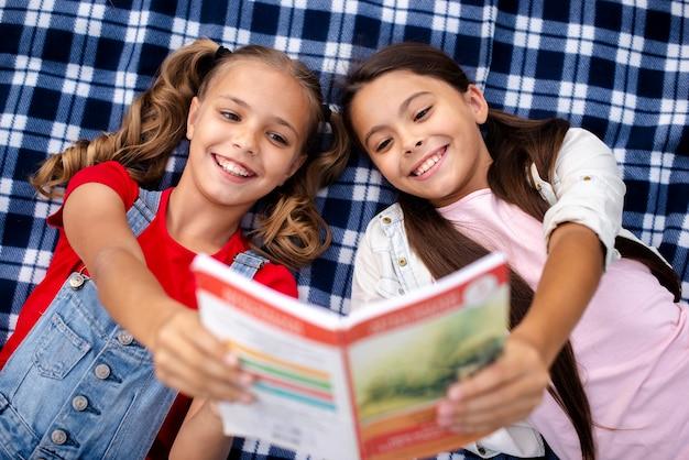 Chicas sonrientes tendido sobre una manta sosteniendo un libro