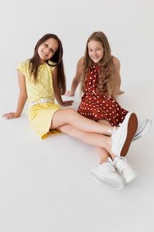 Chicas sonrientes de tiro completo sentados juntos
