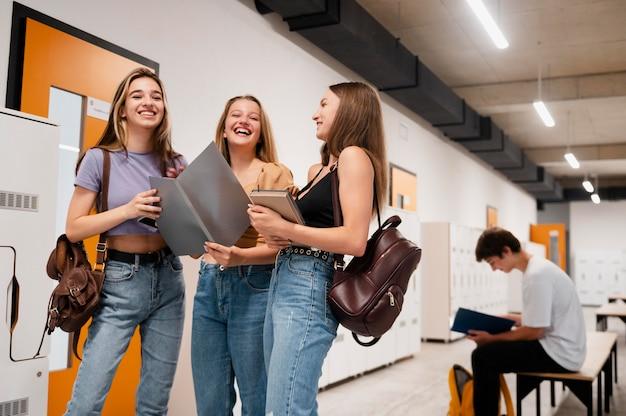 Chicas sonrientes de tiro medio en la escuela