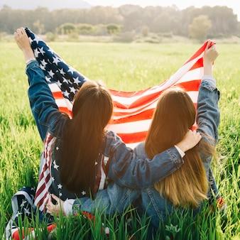 Chicas sosteniendo bandera estadounidense