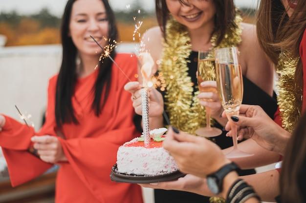 Chicas sosteniendo el pastel de cumpleaños y bengalas en una fiesta