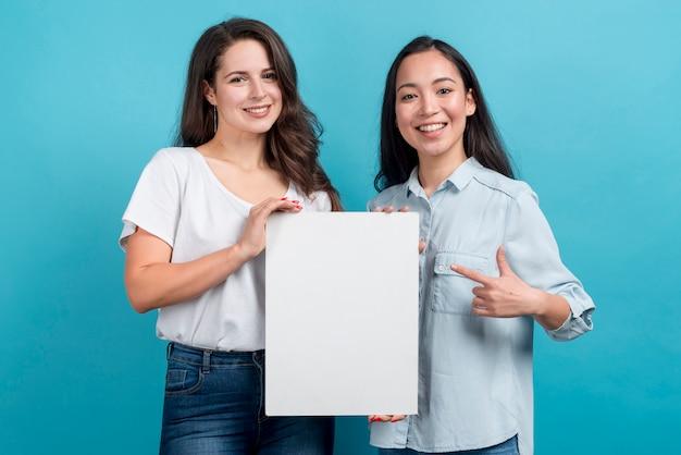 Chicas sujetando tablón en blanco