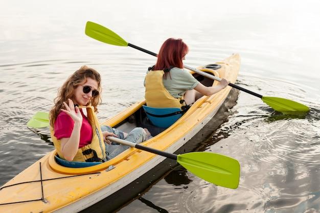 Chicas de tiro completo remando en kayak