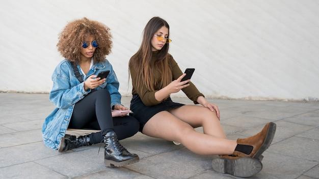Chicas de tiro completo sentados juntos
