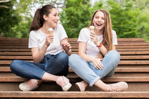 Chicas de tiro largo que tienen un helado en las escaleras