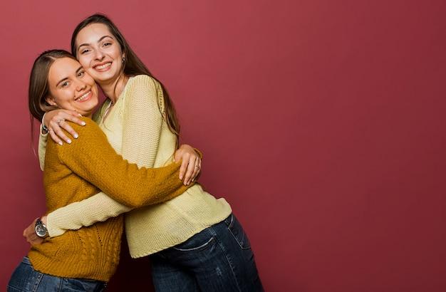 Chicas de tiro medio abrazándose con espacio de copia