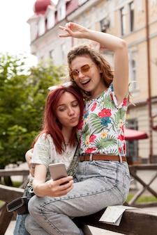 Chicas de tiro medio tomando selfie en el centro de la ciudad