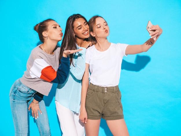 Chicas tomando fotos de autorretrato en el teléfono inteligente. modelos posando junto a la pared azul en el estudio. mujeres mostrando emociones positivas. dan un beso al aire