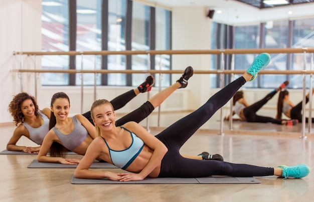 Chicas trabajando acostado de lado en la estera de yoga.
