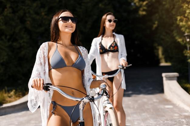 Las chicas en traje de baño andan en bicicleta