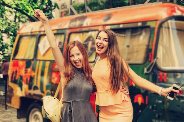 Chicas vestidas se divierten en el fondo de un autobús pintado