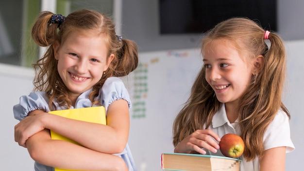 Chicas de vista frontal sonriendo mientras sostienen sus libros