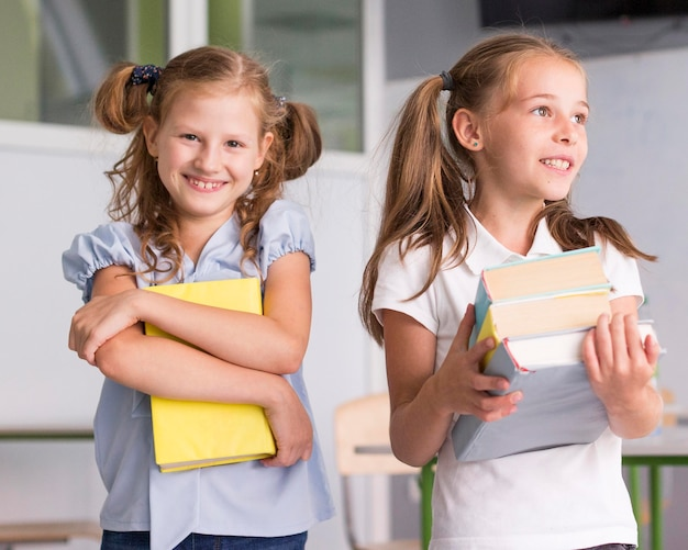 Chicas de vista frontal sosteniendo libros en clase