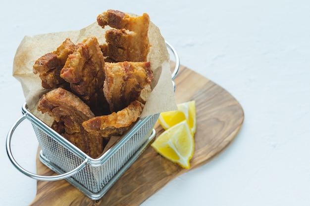 Chicharrones de cerdo frito, en una cesta de metal sobre una superficie blanca. copia espacio
