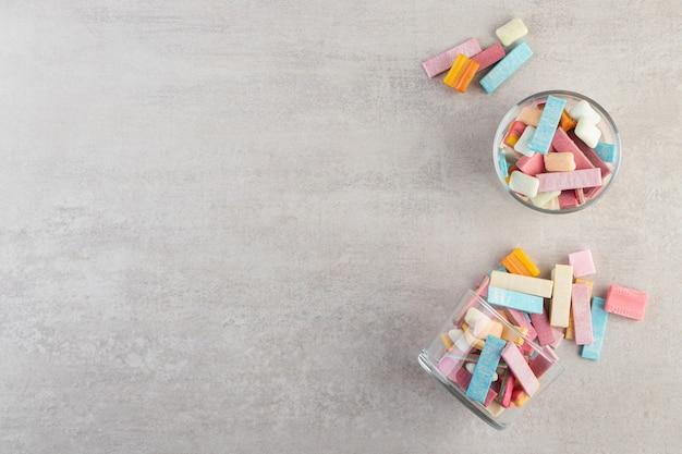 Chicles de colores colocados sobre una mesa de piedra.