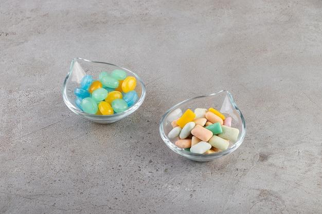 Chicles de colores en tazones colocados sobre una mesa de piedra.