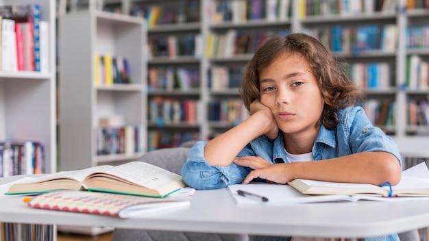 Chico aburrido mientras hace sus deberes con espacio de copia