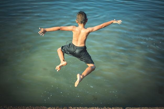 Chico activo saltando en el agua