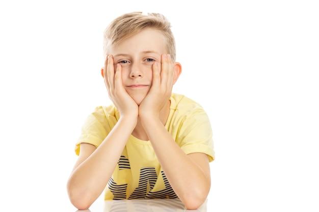 Un chico adolescente con una camiseta amarilla está sentado a la mesa, apoyando su cabeza en sus manos. aislado sobre fondo blanco.