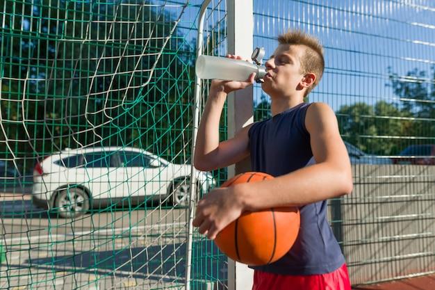 Chico adolescente jugador de baloncesto con pelota bebiendo agua de botella
