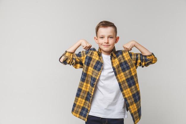 Chico adolescente positivo que muestra la fuerza del cuerpo.