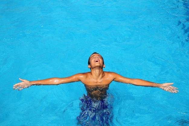 Chico adolescente relajado brazos abiertos azul piscina