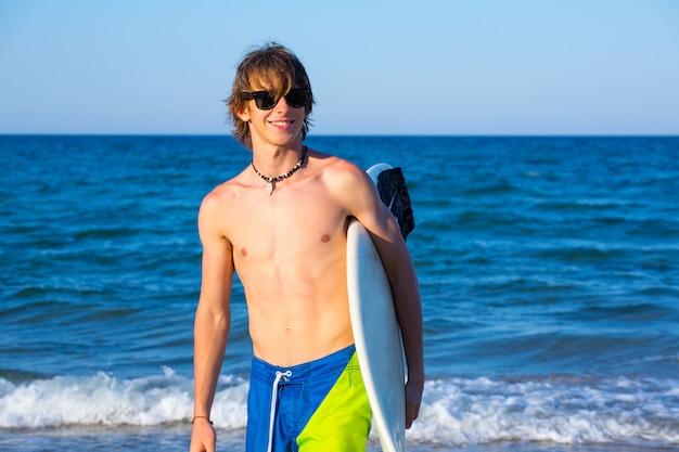 Chico adolescente surfista feliz holing tabla de surf en la playa
