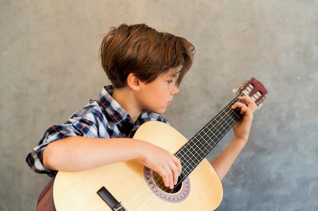 Chico adolescente tocando la guitarra acústica