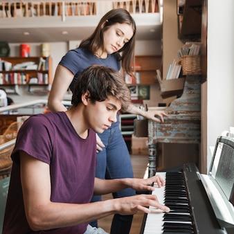 Chico adolescente tocando el piano para novia