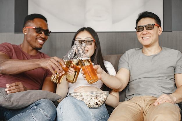 Chico africano y pareja asiática tintinean botellas con una cerveza amigos viendo una película comiendo palomitas de maíz con gafas para una película en 3d
