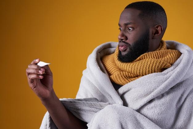 Chico africano sorprendido por el calor del termómetro.
