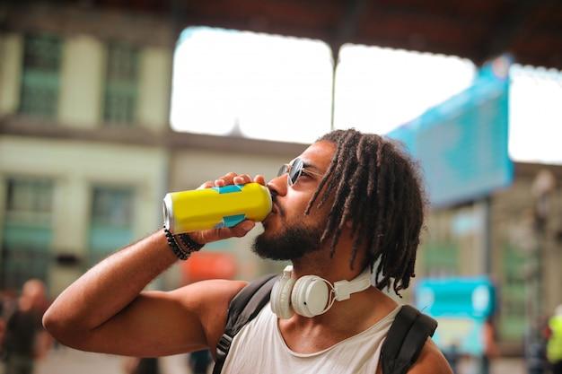 Chico afro bebiendo en la calle