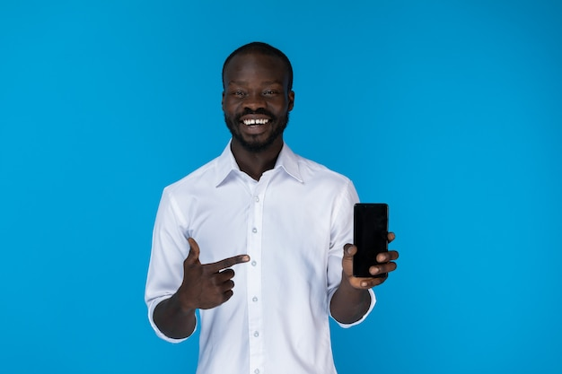Chico afroamericano barbudo está mostrando celular en camisa blanca