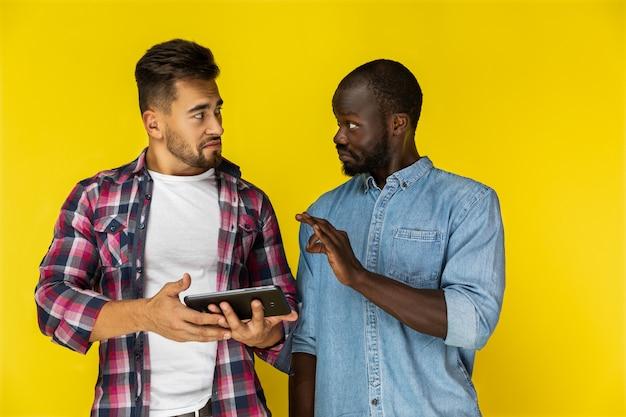 Chico afroamericano está demostrando algo al chico europeo en camisas informales
