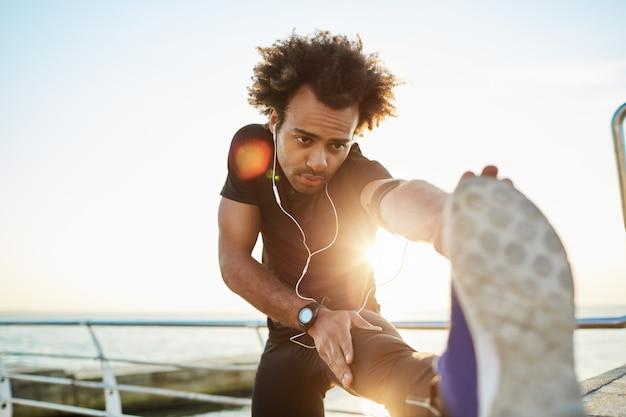 Chico afroamericano deportivo en ropa deportiva negra y zapatillas azules estirando sus músculos