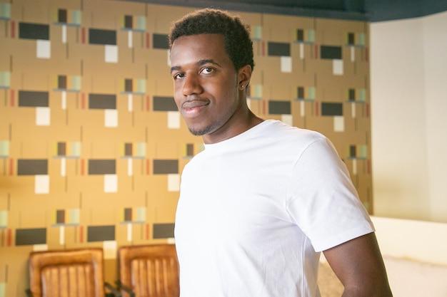 Chico afroamericano guapo positivo en camiseta de pizca de pie y posando en el co-working o el interior de la cafetería, mirando a la cámara