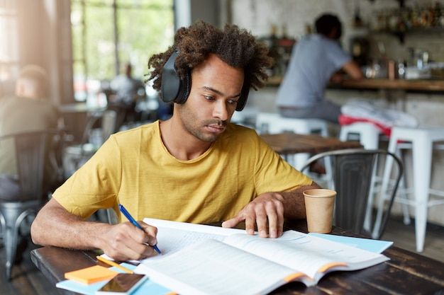 Chico afroamericano hipster con libro y cuaderno escuchando música en auriculares y tomando café mientras está sentado en el acogedor restaurante. concepto de educación
