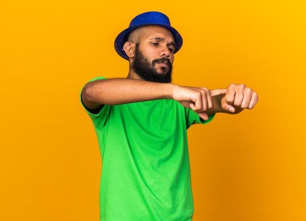 Chico afroamericano joven disgustado con gorro de fiesta mostrando gesto de reloj de pulsera