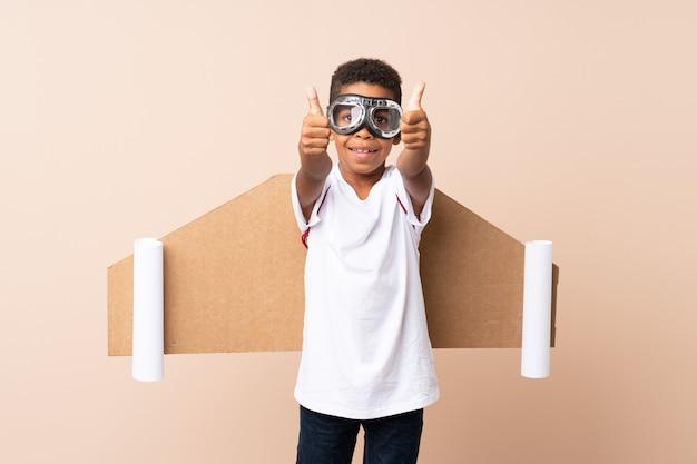 Chico afroamericano con sombrero de aviador y con alas con pulgar arriba sobre pared aislada