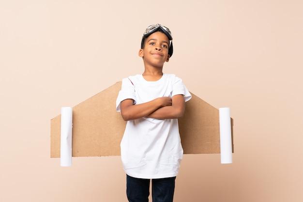 Chico afroamericano con sombrero de aviador y con alas sobre pared aislada
