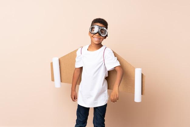 Chico afroamericano con sombrero de aviador y con alas